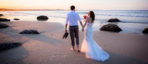 bride and groom walking on Kirra Beach Gold Coast wedding photography