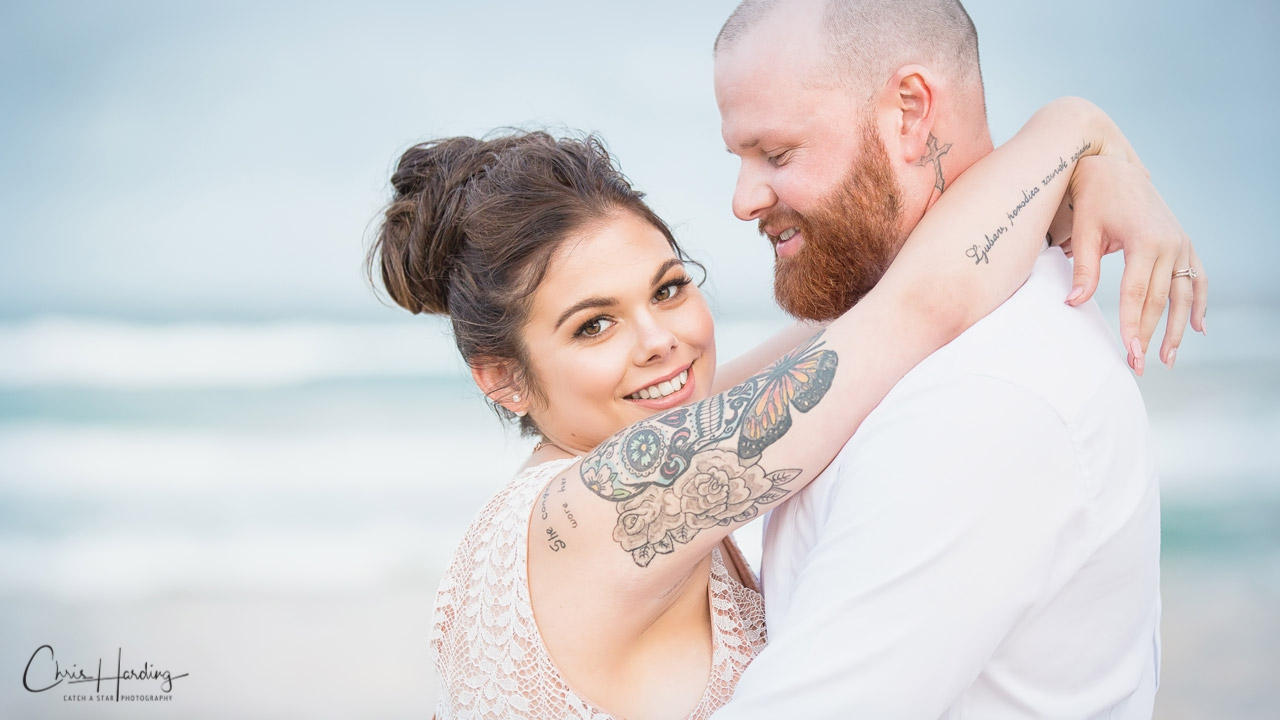 Bride and Groom Embrace on Beach